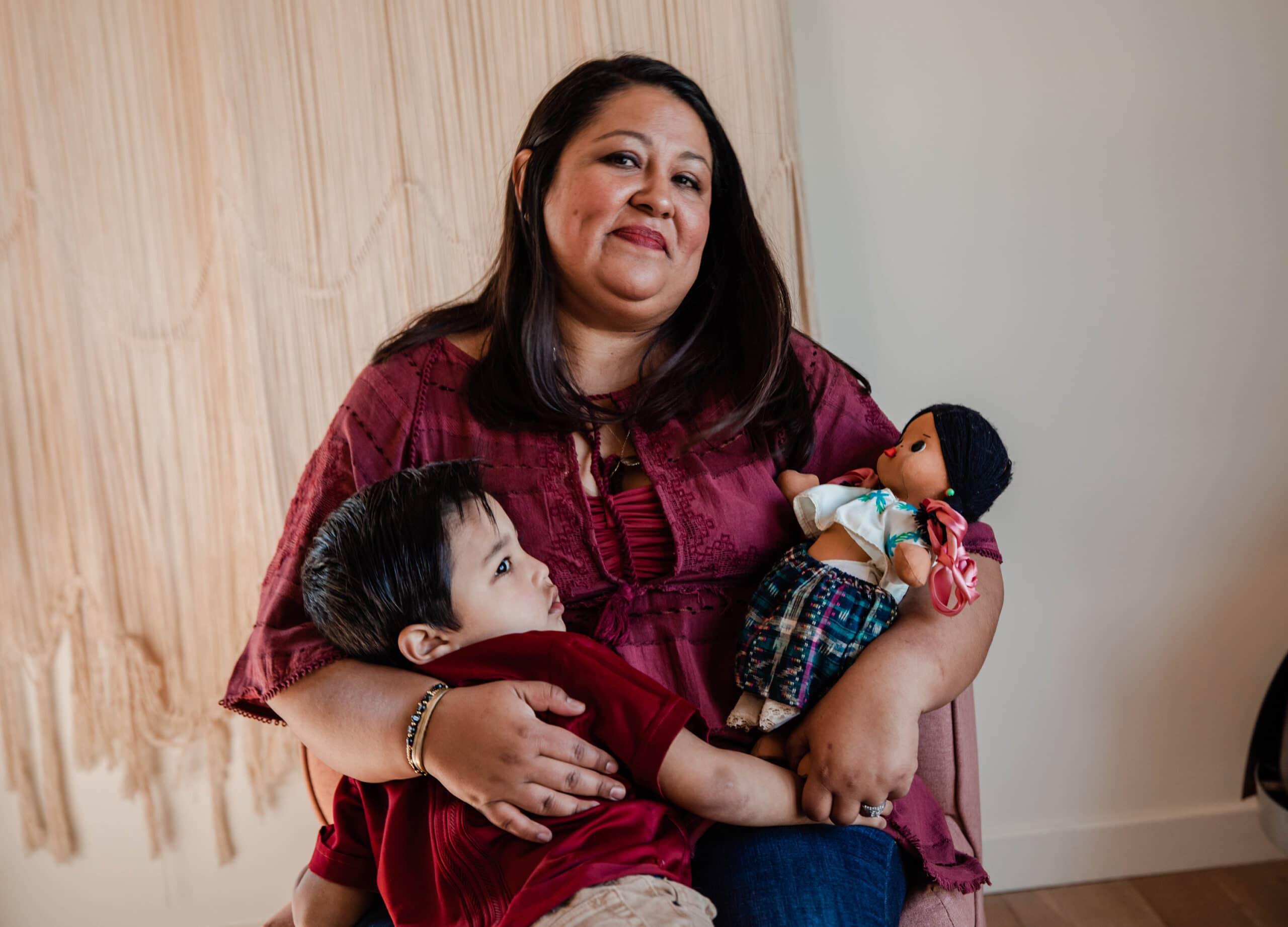 Latino mom hugging her son and a traditional doll